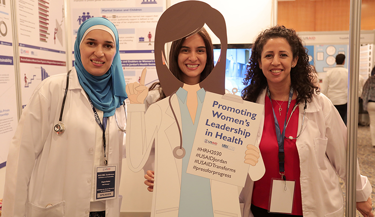 Three women with sign reading - Promoting Women's Leadersip in Health