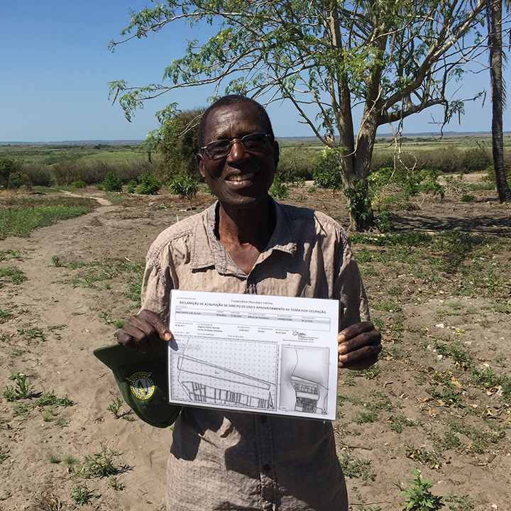 Tanzanian man in field holding up an evaluation chart