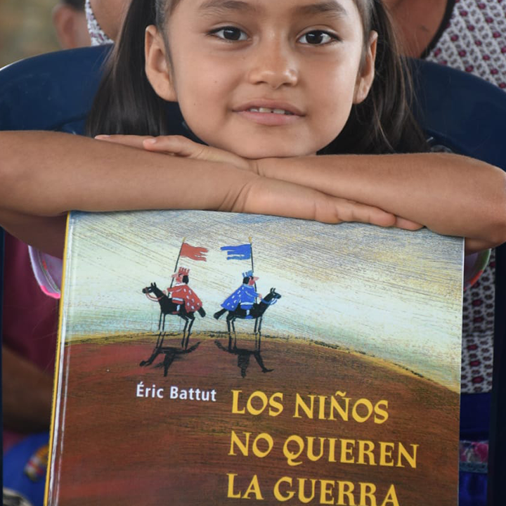 Colombian girl leans on book about peace