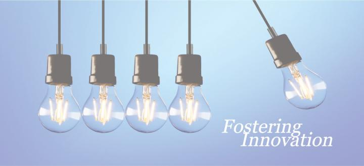 "Five lit lightbulbs with one swinging away beside the text, ""Fostering Innovation"""