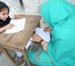 Women and girl in hijabs sitting at wooden desk and reading documents.