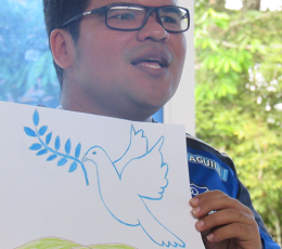 Man holding picture of hand drawn dove