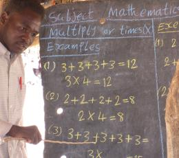South Sudanese man in front of chalk board full of math problems