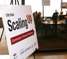 "Sign reads ""Scaling Up,"" pointing to a conference room of people."