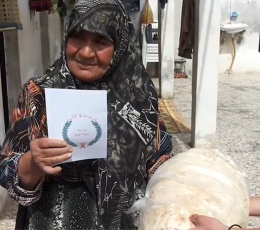 Syrian woman holds up paper with drawing