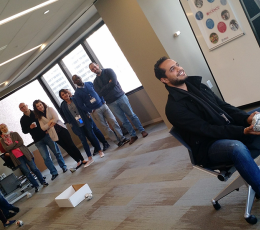 Man on chair facing away from group of colleagues behind him