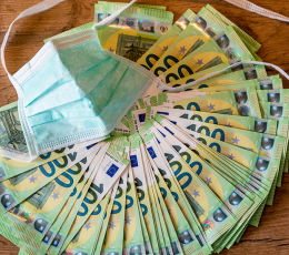 Surgical mask lays on top of stack of 100 Euro notes
