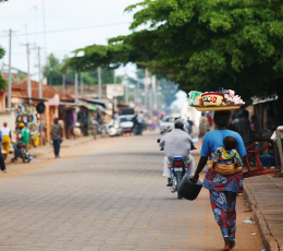 Woman with child on her back walks down busy street in Benin