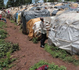 Man adjusts tent in informal IDP settlement in Kenya